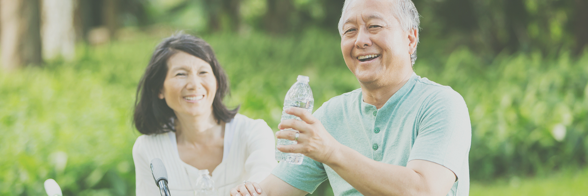 Older couple enjoying water after a bike ride